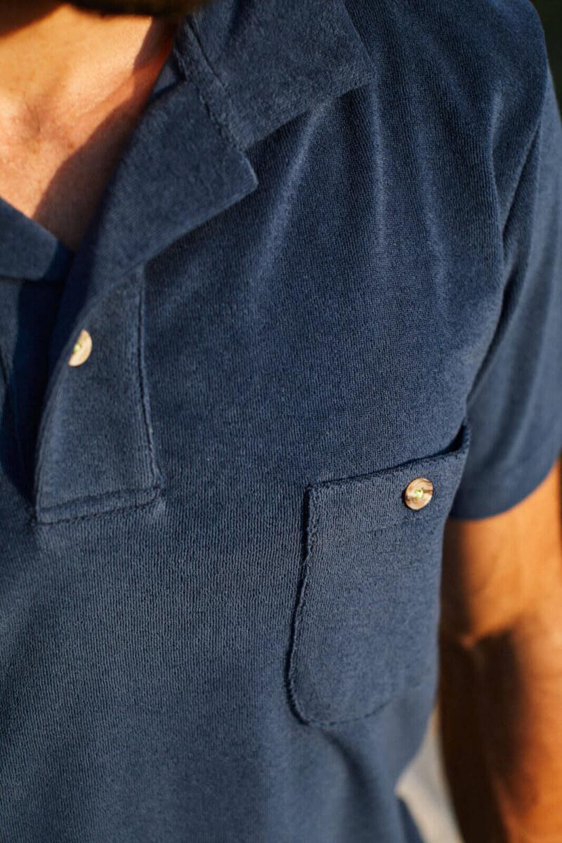 man wearing a navy terry cloth polo