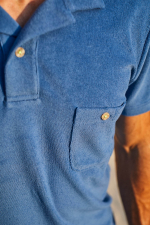 man wearing a blue terry cloth polo
